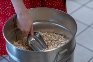 A woman fills cereal grains, detail from an unwrapped shop.