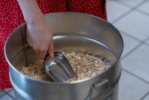 Eine Frau füllt Getreidekörner ab, Detail aus einem Unverpacktladen.