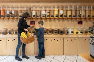 """Eine Frau und ein Junge stehen vor einem Regal mit Abfüllbehältern für Getreide im verpackungsfreien Laden """"Frau Erna`s loser LebensMittelpunkt"""" in Magdeburg, Deutschland"""