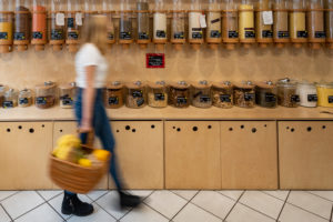 A young customer walks past a shelf with filling containers for grain, detail from an unwrapped shop.