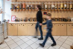 Eine Frau und ein Junge gehen an einem Regal mit Abfüllbehältern für Getreide vorbei, Szene aus einem Unverpacktladen.