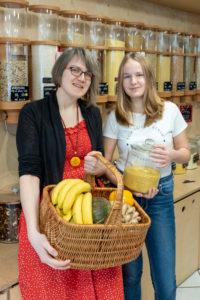 """Eine Frau und eine Schülerin stehen vor einem Regal mit Abfüllbehältern für Getreide im verpackungsfreien Laden """"Frau Erna`s loser LebensMittelpunkt"""" in Magdeburg, Deutschland"""