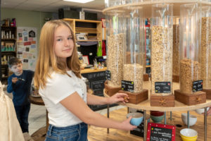 A young customer stands in front of a shelf with filling containers for muesli in an unpacked shop.