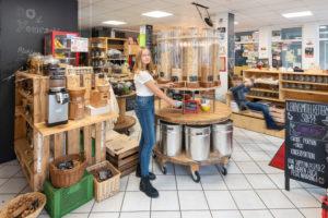 Eine junge Kundin steht vor einem Regal mit Abfüllbehältern für Müsli in einem Unverpacktladen. Rechts daneben schaukelt ein Junge. Szene aus einem Unverpacktladen.