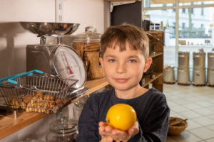 A boy is standing on a scale in an unpacked shop. He is holding a lemon in his hands.
