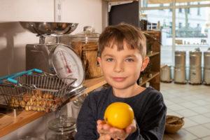 Eine Junge steht in einem Unverpacktladen an einer Waage. Er hält eine Zitrone in den Händen.