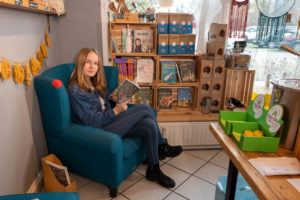 A young customer is sitting in the reading corner of an unpackaged shop, where you can buy books about zero waste.