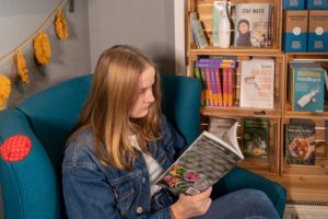 Eine junge Kundin sitzt in der Leseecke eines Unverpacktladens, in dem es Bücher über Zero Waste zu kaufe gibt.