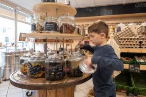 Eine Junge füllt sich in einem Unverpacktladen Süßigkeiten ab.
