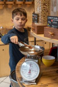 Eine Junge steht in einem Unverpacktladen an einem Regal mit Abfüllbehältern für Cerealien. Er wiegt Haselnüsse ab.