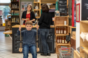 A boy swings in an unpacked shop. The owner advises a customer in the background.