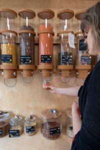 Die Inhaberin eines Unverpacktladens steht an einem Regal mit Abfüllbehältern für Getreide.