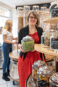 A woman is holding a jar of candy in her hands in an unpackaged shop. In the background a young customer is standing on a shelf with filling containers for grain.