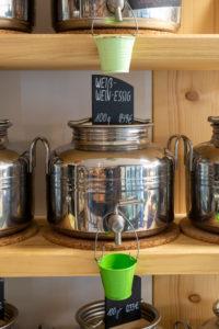 Behälter zum Abfüllen von Essig, Rapsöl und Olivenöl. Detail aus einem Unverpacktladen.