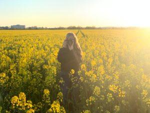 Junges Mädchen steht steht zur Abendsonne mit einem Fotoapparat im Rapsfeld