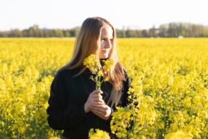 Young girl stands in the evening sun in the rapeseed field