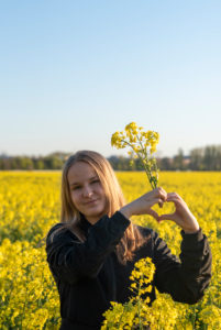 Young girl stands by the evening sun in the rape field and forms a heart
