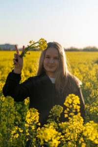 Young girl is standing in a rapeseed field