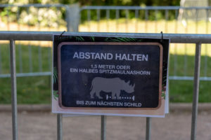 "Germany, Saxony-Anhalt, Magdeburg, entrance to the zoo with the sign ""Keep your distance"", 1.5 meters or half a black rhinoceros."
