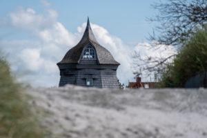 Deutschland, Mecklenburg-Vorpommern, Hiddensee, eine alte Windmühle steht hinter dem Deich in dem Fischerdorf Vitte.