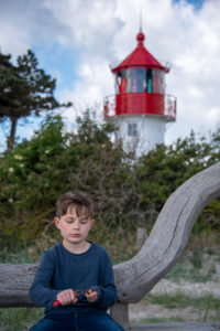 Germany, Mecklenburg-West Pomerania, Hiddensee, boy carves in front of the Gellen lighthouse, which stands on a grass dune. Blue sky with clouds in the background, Baltic Sea.