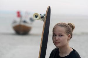 Mädchen mit Longboard steht vor einem Fischerboot