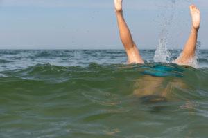 Deutschland, Mecklenburg-Vorpommern, Insel Rügen, Ostseebad Binz, Beine eines Jungen gucken aus dem Wasser, Ostsee