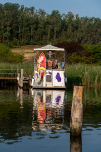 Deutschland, Mecklenburg-Vorpommern, Ostseebad Sellin, Seedorf, ein Motorschiff mit lila Kuhflecken liegt im Naturhafen.