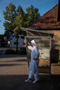 Imker steht an einer Bushaltestelle