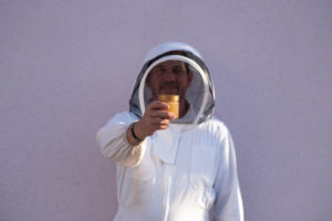 Beekeeper holds a honey jar in his hand