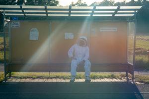 Imker sitzt in einer Bushaltestelle