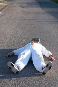 Beekeeper lies on an asphalt road
