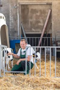 Landwirt, Bauer, streichelt eine Kälbchen