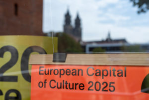 Germany, Saxony-Anhalt, Magdeburg, posters to advertise the state capital Magdeburg hang in a shop window in which the cathedral is reflected. Alongside Chemnitz, Hanover, Hildesheim and Nuremberg, Magdeburg is applying for the title of European Capital of Culture 2025.