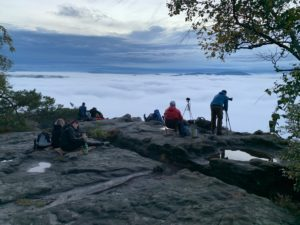 Germany, Saxony, photographers sit on the rocks of the Lilienstein and wait for the sunrise, thick clouds of mist move over the Elbe Sandstone Mountains.
