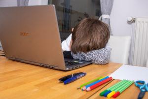 Junge sitzt im Homeschooling vor einem Laptop