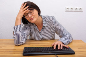 Businesswoman sitting desperately in front of a computer keyboard