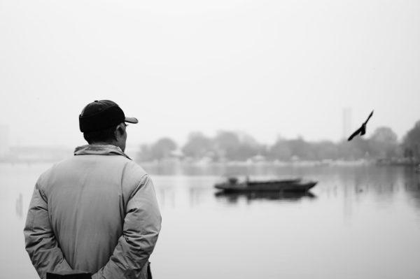 An elderly man staning in front of a lake in China looking into the distance