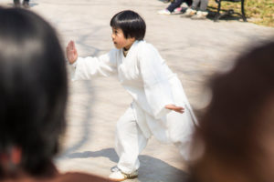 A boy practicing Qigong in the middle of a group of people in Nanjing, China