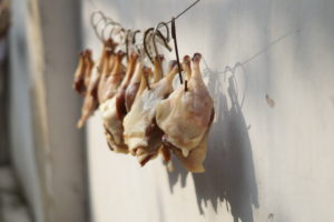 Chicken hanging on hooks to dry outside