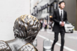A businessman in a suit beeing watched from a statue