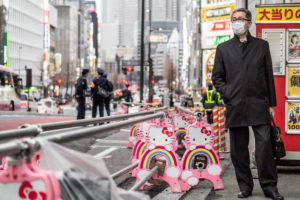 A serious businessman with surgical mask next to a 'Hello Kitty'- road barrier