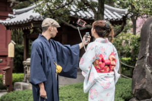Two people taking selfies in a temple complex in Tokyo