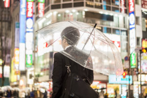 A businessman with an umbrella in the brightly lit streets in the evening