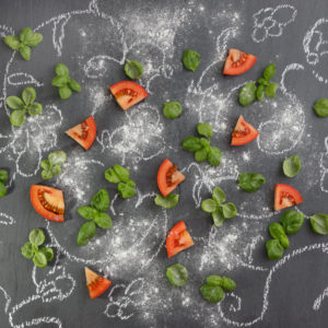 Tomatoes with basil on notice board painted with chalk