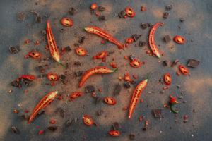 Rote Chilischoten mit Kakaopulver und Schokolade