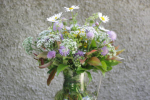 Bouquet of meadow flowers 'impressionistic' in front of a roughly structured wall