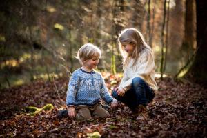 Junge und Mädchen spielen im Herbstwald