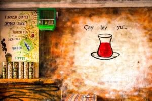Teehaus, türkisches Teeglas an die Wand gemalt,  Wellensittich im Käfig, warme Farben