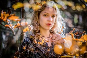 junge Frau mit blonden Haaren im Wald, ernster und nachdenklicher Blick